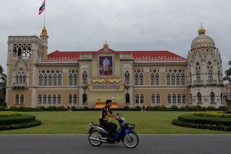A police officer rides his motorcycle past a picture of Thailand's King Maha Vajiralongkorn Bodindradebayavarangkun installed at the Government House in Bangkok
