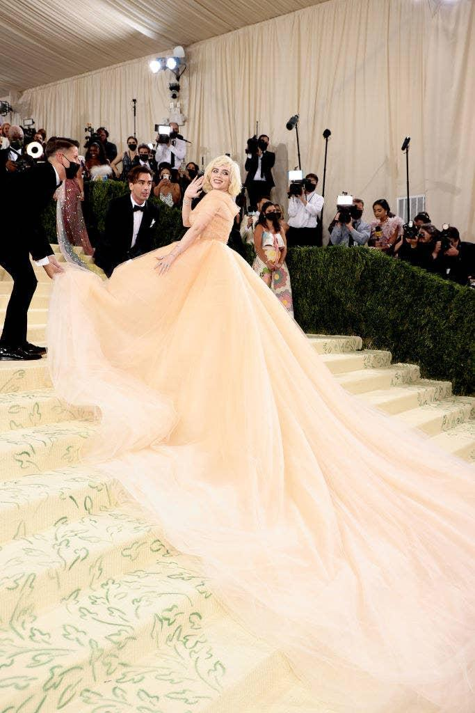 Billie stands on the steps of the Met Gala in a ball gown with an off-shoulder neckline and Marilyn Monroe-inspired hair