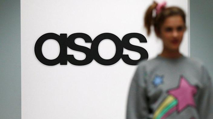 A model walks on a catwalk with an Asos logo in the background