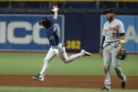 Tampa Bay Rays' Brett Phillips, left, circles the bases after hitting a three-run home run as Detroit Tigers second baseman Harold Castro (30) walks off the filed during the 10th inning of a baseball game Friday, Sept. 17, 2021, in St. Petersburg, Fla. (AP Photo/Scott Audette)