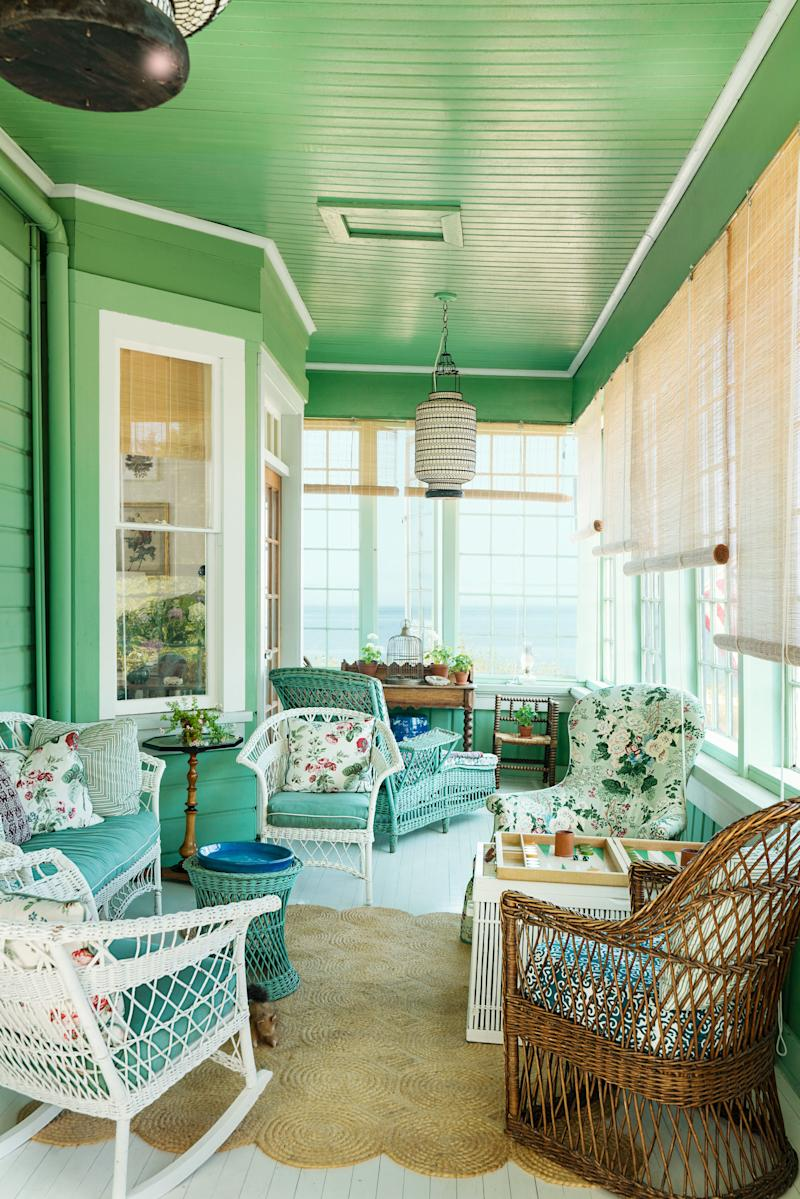 The sunporch features vintage painted wicker seating.