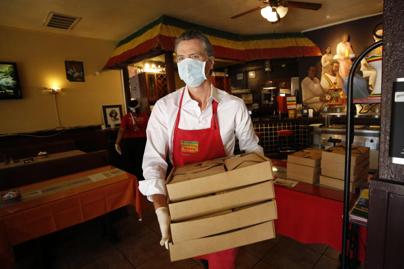California Gov. Gavin Newsom carries meals made at the Queen Sheba Ethiopian Cuisine restaurant, to a waiting delivery vehicle in Sacramento, Calif., Friday, June 19, 2020. Newsom visited the restaurant that is participating in the Great Plates Delivered program that provides meals to older adults who are at-risk to COVID-19. (AP Photo/Rich Pedroncelli, Pool)