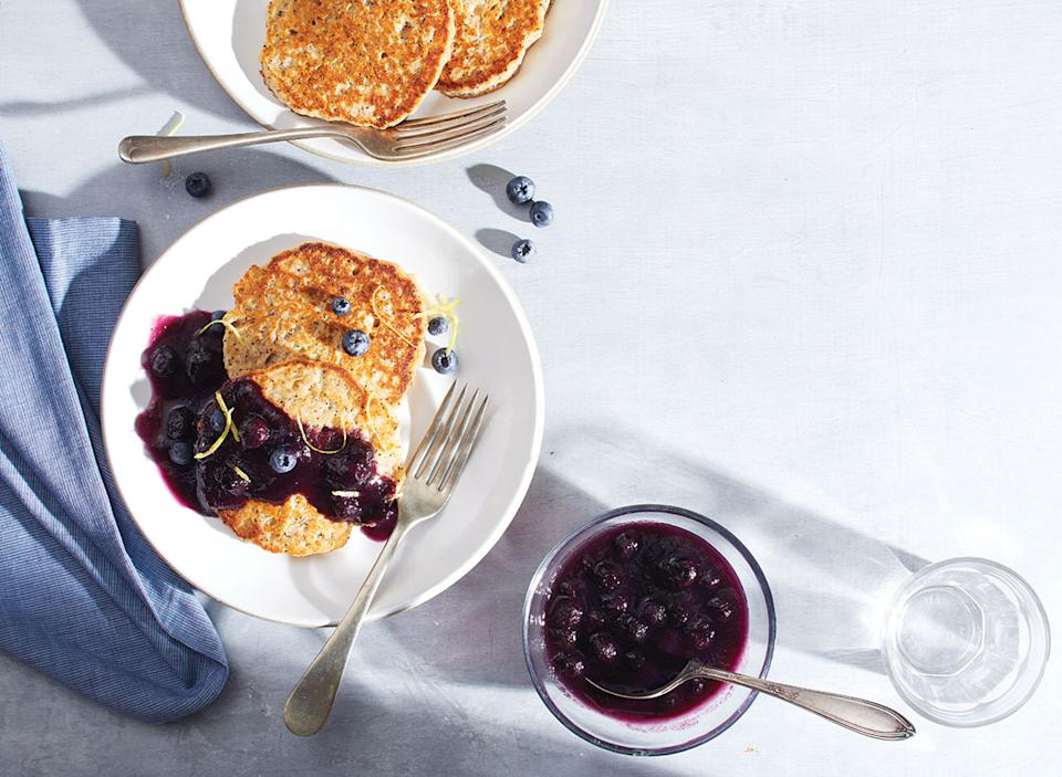 lemon poppy seed pancakes with blueberry compote on white plate with fork, spoon, blue cloth napkin