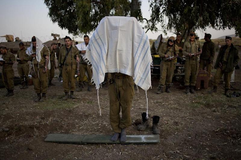An Israeli soldier of the Golani brigade covers himself in a prayer shawl as others gather for the morning prayer before a military exercise in the Israeli controlled Golan Heights, near the border with Syria, Tuesday, May 7, 2013. (AP Photo/Ariel Schalit)