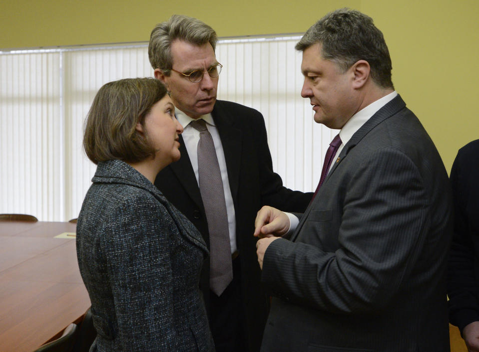 FILE - In this Dec. 10, 2013, file photo, U.S. Assistant Secretary for European and Eurasian Affairs Victoria Nuland, left, and U.S. Ambassador in Ukraine Geoffrey R. Pyatt, center, speak with Ukrainian lawmaker and opposition leader Petro Poroshenko in Kyiv, Ukraine. When Secretary of State Antony Blinken travels to Ukraine he'll be carrying a tough anti-graft message and strong U.S. backing for the country's response to Russian aggression. He'll also be bringing along a familiar face in the Washington-Moscow tug-of-war over Ukraine: Victoria Nuland. The mere presence in Kyiv of Nuland, now the No. 3 State Department official, is likely to irritate Russia. (AP Photo/Andrew Kravchenko, Pool, File)