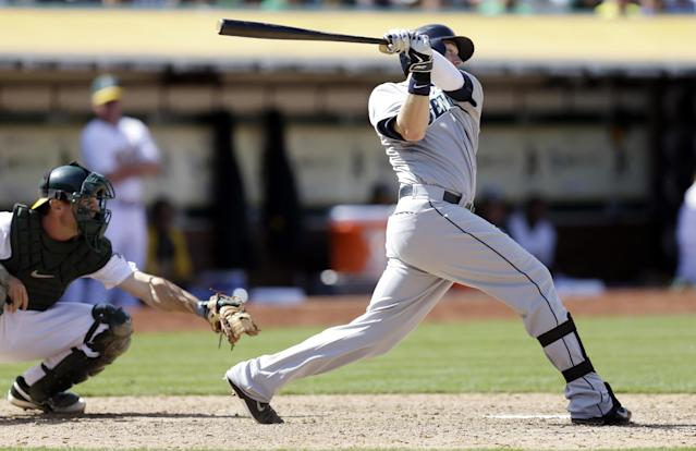 Seattle Mariners' Justin Smoak hits an RBI single off Oakland Athletics' Dan Otero in the tenth inning of a baseball game Wednesday, May 7, 2014, in Oakland, Calif. (AP Photo/Ben Margot)