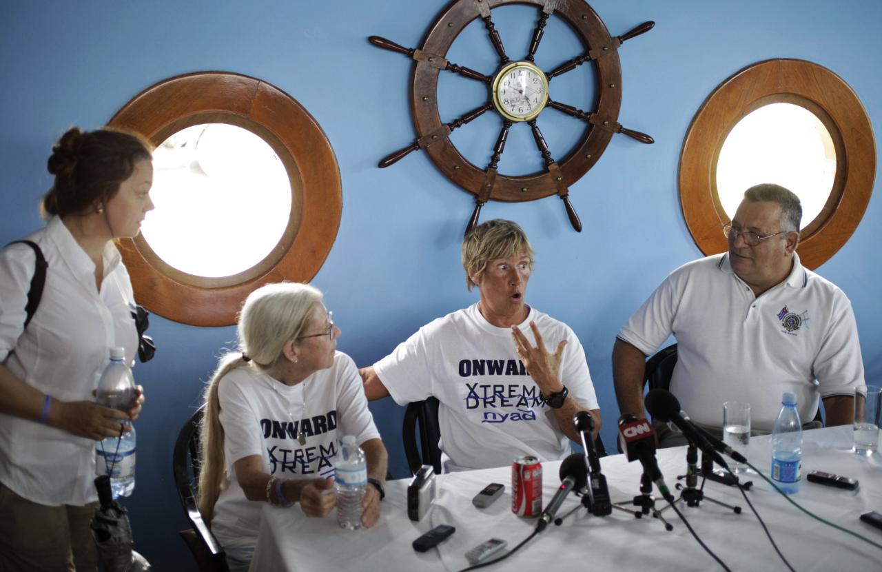 U.S. endurance swimmer Diana Nyad (C) speaks during a news conference in Havana August 30, 2013. Nyad said on Friday she will set off this weekend from Cuba for Florida, better prepared for the sharks, venomous jellyfish and powerful Gulf Stream currents that foiled her previous four attempts at the 103 mile (166-km) crossing. If she succeeds, the 64-year-old would become the first person to make the crossing without a shark cage. Instead, equipment emitting a mild electric current in the water will keep sharks at bay. Nyad would also become the world record holder for the longest unassisted open ocean swim, meaning no shark cage protected her during the ordeal that is expected to take more than 60 hours. REUTERS/Enrique De La Osa (CUBA - Tags: SPORT SWIMMING)