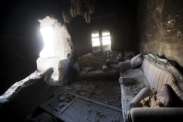 FILE - An apartment destroyed by tank shelling is seen in a building in the Karm al-Jabel neighborhood after several days of intense clashes between rebel fighters and the Syrian army in Aleppo, Syria, Oct. 28, 2012. This image was one in a series of 20 by AP photographers that won the 2013 Pulitzer Prize in Breaking News Photography. (AP Photo/Narciso Contreras, File)