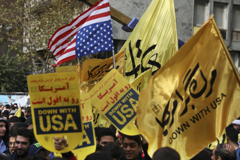 """Demonstrators hold anti-U.S. banners and a torn makeshift U.S. flag upside down in an annual rally in front of the former U.S. Embassy in Tehran, Iran, Monday, Nov. 4, 2019. Reviving decades-old cries of """"Death to America,"""" Iran on Monday marked the 40th anniversary of the 1979 student takeover of the U.S. Embassy in Tehran and the 444-day hostage crisis that followed as tensions remain high over the country's collapsing nuclear deal with world powers. (AP Photo/Vahid Salemi)"""