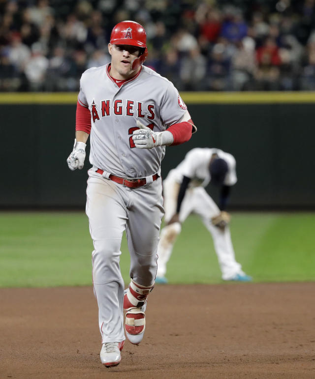 Los Angeles Angels' Mike Trout rounds the bases as Seattle Mariners second baseman Dee Gordon rests behind him after Trout hit a two-run home run during the seventh inning of a baseball game, Tuesday, June 12, 2018, in Seattle. It was Trout's second home run of the game. (AP Photo/Ted S. Warren)