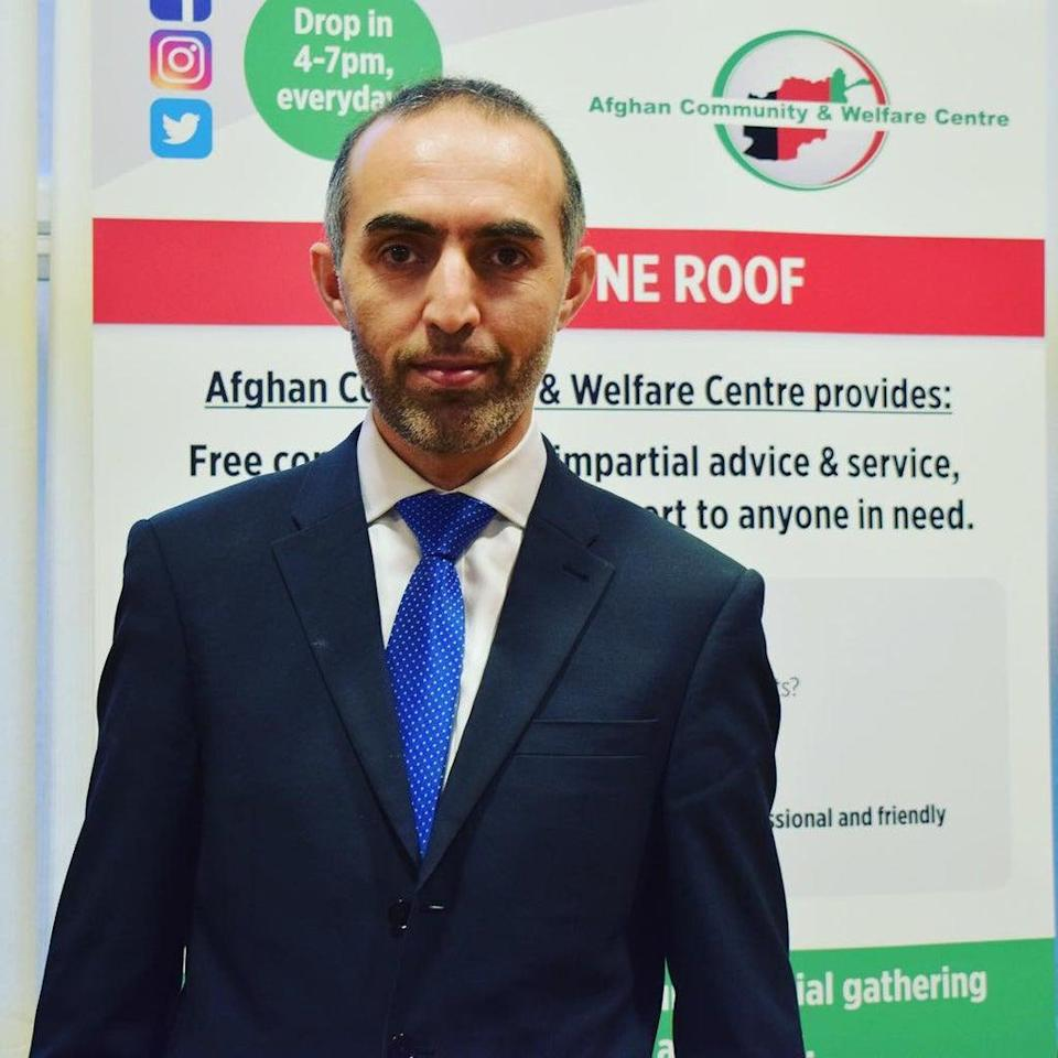 Fahim Zazai standing in front of a poster with details about the Afghan Community and Welfare Centre on it (Fahim Zazai/PA).