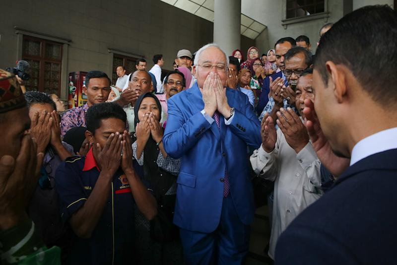 Former prime minister Datuk Seri Najib Razak prays with supporters at the Kuala Lumpur Courts Complex December 3, 2019. — Picture by Yusof Mat Isa