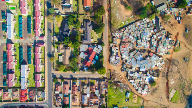 <p>Spacious mansions sit just across the road from where people live in poverty in South Africa (MediaDrumWorld/Johnny Miller) </p>