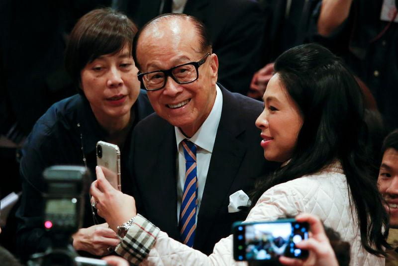 Hong Kong tycoon Li Ka-shing takes a selfie with journalists after announcing his retirement in Hong Kong