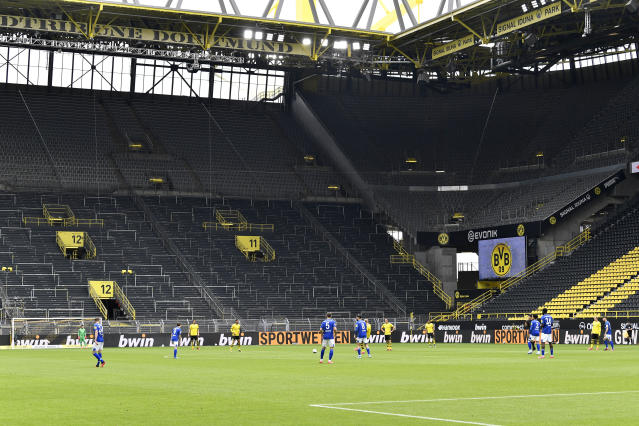 Schalke, foreground and Dortmund players play in an empty stadium during the German Bundesliga soccer match between Borussia Dortmund and Schalke 04 in Dortmund, Germany, Saturday, May 16, 2020. The German Bundesliga becomes the world's first major soccer league to resume after a two-month suspension because of the coronavirus pandemic. (AP Photo/Martin Meissner, Pool)