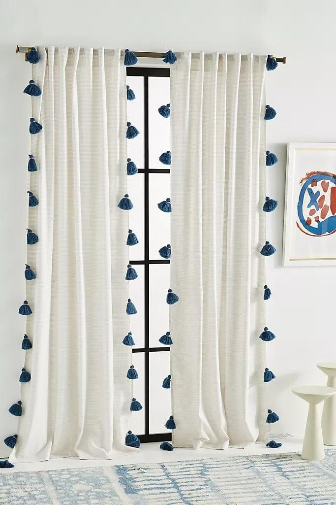 """<p>I am so happy with these <a href=""""https://www.popsugar.com/buy/Anthropologie-Mindra-Curtains-575410?p_name=Anthropologie%20Mindra%20Curtains&retailer=anthropologie.com&pid=575410&price=78&evar1=casa%3Aus&evar9=47486578&evar98=https%3A%2F%2Fwww.popsugar.com%2Fphoto-gallery%2F47486578%2Fimage%2F47486768%2FAnthropologie-Mindra-Curtain&list1=shopping%2Cfurniture%2Ceditors%20pick%2Capartments%2Chome%20decorating%2Csmall%20space%20living%2Capartment%20living%2Cdecor%20shopping%2Chome%20shopping%2Cat%20home%20with%20popsugar&prop13=api&pdata=1"""" class=""""link rapid-noclick-resp"""" rel=""""nofollow noopener"""" target=""""_blank"""" data-ylk=""""slk:Anthropologie Mindra Curtains"""">Anthropologie Mindra Curtains</a> ($78, originally $108 each) - the lightweight fabric brightens up the room and the pom-poms add some personality.</p>"""