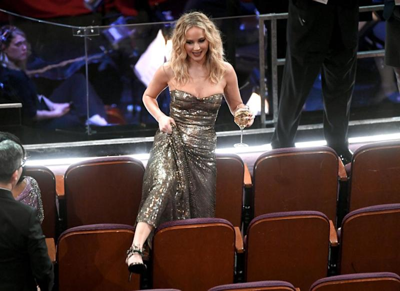 Trying to be oh-so savvy and clever, JLaw lifted up her gown to give her legs more room to move as she attempted to climb over. Source: Getty
