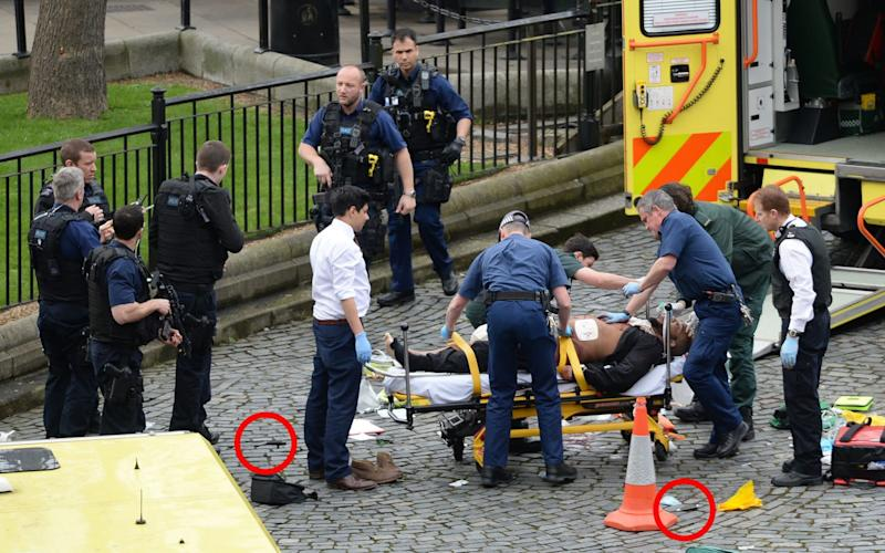 The suspected London terror attacker being treated by paramedics, with the knives used in the assault circled. - Credit: PA