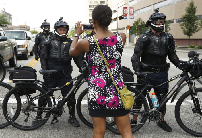 <p>A demonstrator takes a picture of the police line during the Shut Down Trump and the RNC protest on Sunday, July 17, 2016, in Cleveland, Ohio. (Photo: John Minchillo/AP)</p>