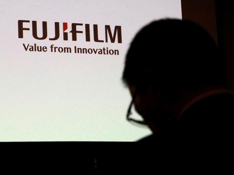 A man is silhouetted in front of Fujifilm Holdings' logo ahead of its news conference in Tokyo