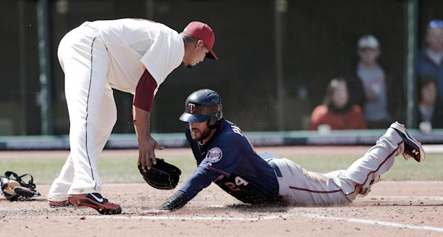 Minnesota Twins' Trevor Plouffe, bottom, scores as Cleveland Indians starting pitcher Carlos Carrasco waits for the ball in the third inning of a baseball game, Saturday, April 5, 2014, in Cleveland. Plouffe scored on catcher Yan Gomes passed ball. (AP Photo/Tony Dejak)
