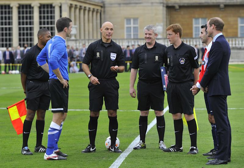The Duke of Cambridge (right) watches as referee Howard Webb (third left) tosses the coin before the Southern Amateur League football match between Polytechnic FC and Civil Service FC in Buckingham Palace's garden, central London Monday Oct. 7, 2013. The Duke of Cambridge, president of the FA, helped organise the event, the first of its kind at Queen Elizabeth II's London home, as part of the Football Association's 150th anniversary celebrations. (AP Photo/ Toby Melville, Pool)