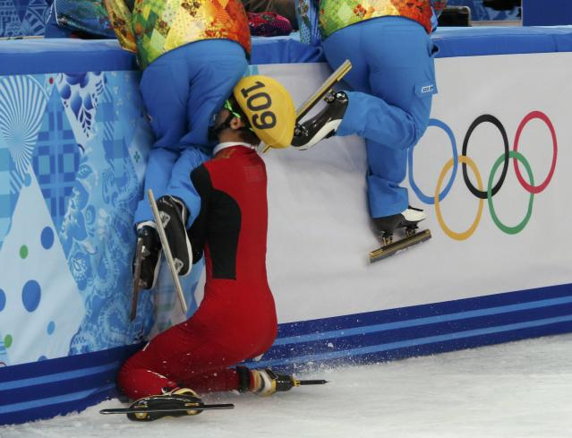 Olympic officials who maintain the ice jump out of the way as China's Kexin Fan crashes out into the barrier women's 500 metres short track speed skating semifinal event at the Iceberg Skating Palace during the 2014 Sochi Winter Olympics February 13, 2014. REUTERS/David Gray (RUSSIA - Tags: OLYMPICS SPORT SPEED SKATING)