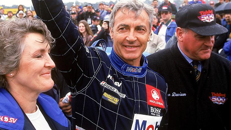 Peter Brock is pictured waving to fans in 1997, alongside then wife Bev.