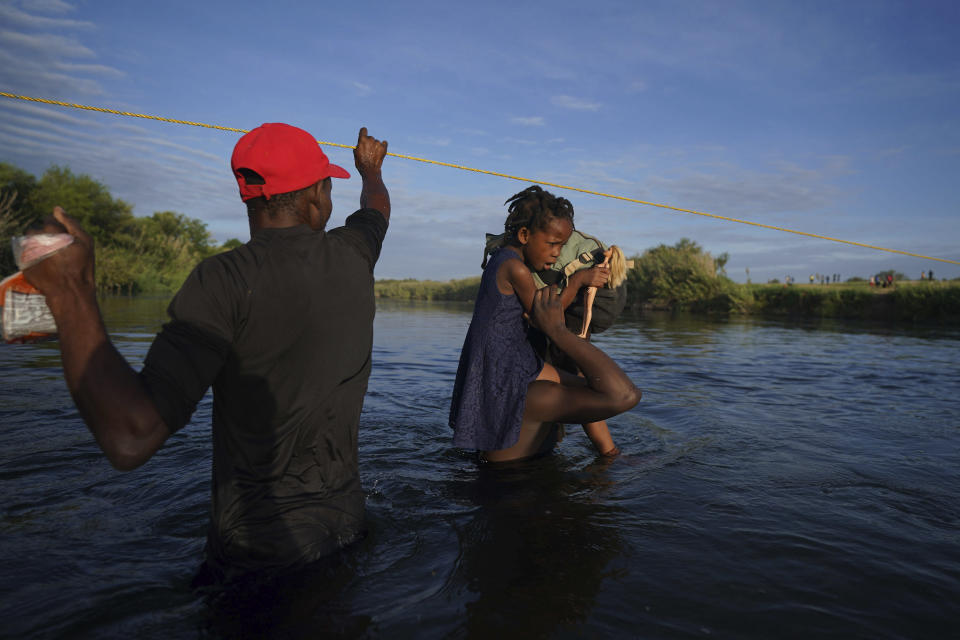 A little girl holds on to her Barbie doll as she is carried over the Rio Grande river to Del Rio, Texas, as some migrants, many from Haiti, wade across in the opposite direction to return to Ciudad Acuna, Mexico, early Wednesday, Sept. 22, 2021, some to avoid possible deportation from the U.S. and others to load up with supplies. (AP Photo/Fernando Llano)