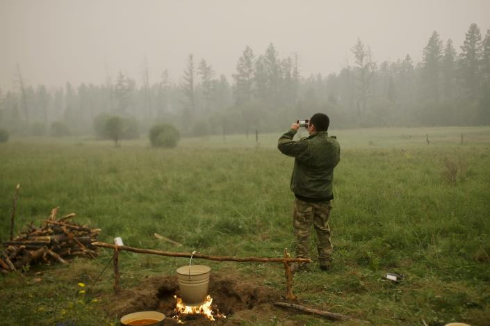 A member of volunteers crew monitors the fire from spreading at Gorny Ulus area west of Yakutsk, Russia, Tuesday, July 20, 2021. The hardest hit area is the Sakha Republic, also known as Yakutia, in the far northeast of Russia, about 5,000 kilometers (3,200 miles) from Moscow. Volunteers have joined over 5,000 regular firefighters in the effort, motivated by their love of the vast region. The volunteers rely on their own money or funds from nongovernmental groups. (AP Photo/Ivan Nikiforov)
