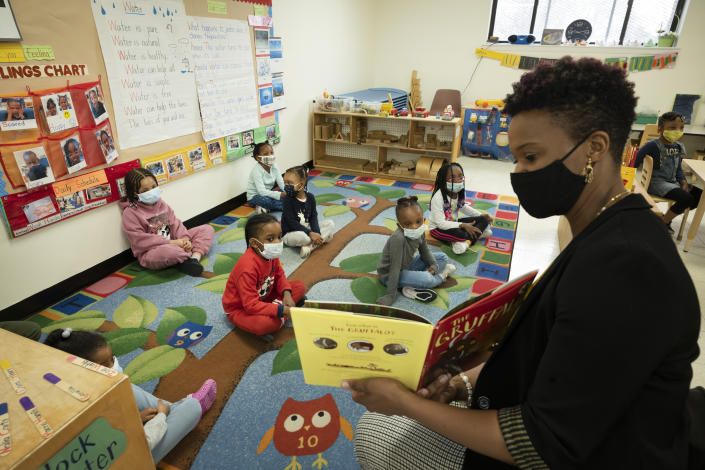 Parent Melissa Jean reads a book to a pre-K class, all wearing face masks.