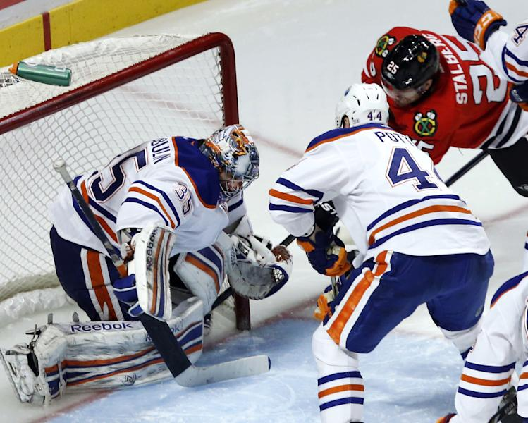 Chicago Blackhawks left wing Viktor Stalberg (25) stuff the puck in the net past Edmonton Oilers goalie Nikolai Khabibulin (35), of Russia, and Corey Potter for a goal during the third period of an NHL hockey game, Monday, Feb. 25, 2013, in Chicago. The Blackhawks won 3-2 in overtime. (AP Photo/Charles Rex Arbogast)