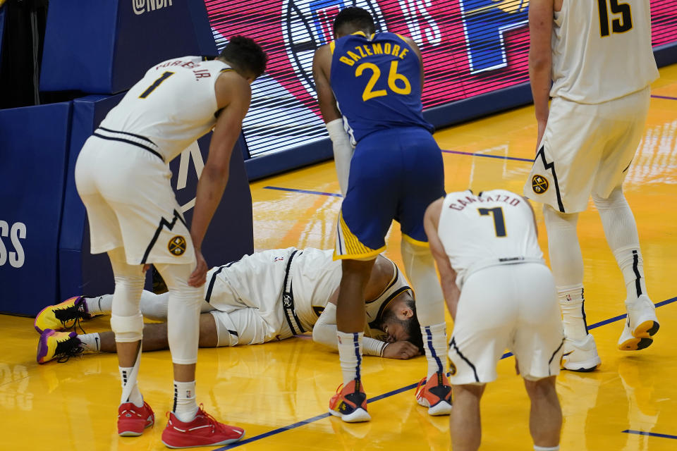 Players watch as Denver Nuggets guard Jamal Murray remains on the floor after being injured during the second half of an NBA basketball game against the Golden State Warriors in San Francisco, Monday, April 12, 2021. (AP Photo/Jeff Chiu)