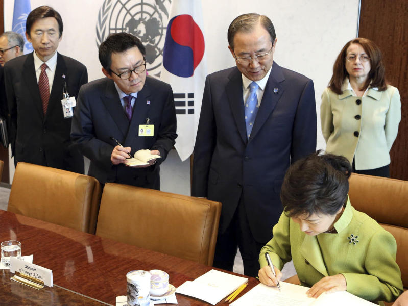"In this May 6, 2013 photo, South Korean President's spokesman Yoon Chang-jung, third right top, watches South Korean President Park Geun-hye, right bottom, sign the guestbook as UN Secretary General Ban Ki-moon, second right, looks on, at United Nations headquarters. President Park's office says she has fired her chief spokesman Yoon after a ""disgraceful incident"" during Park's trip to the United States. Media reports say the spokesman was accused of sexual abuse. (AP Photo/Yonhap, Do Kwang-hwan) KOREA OUT"