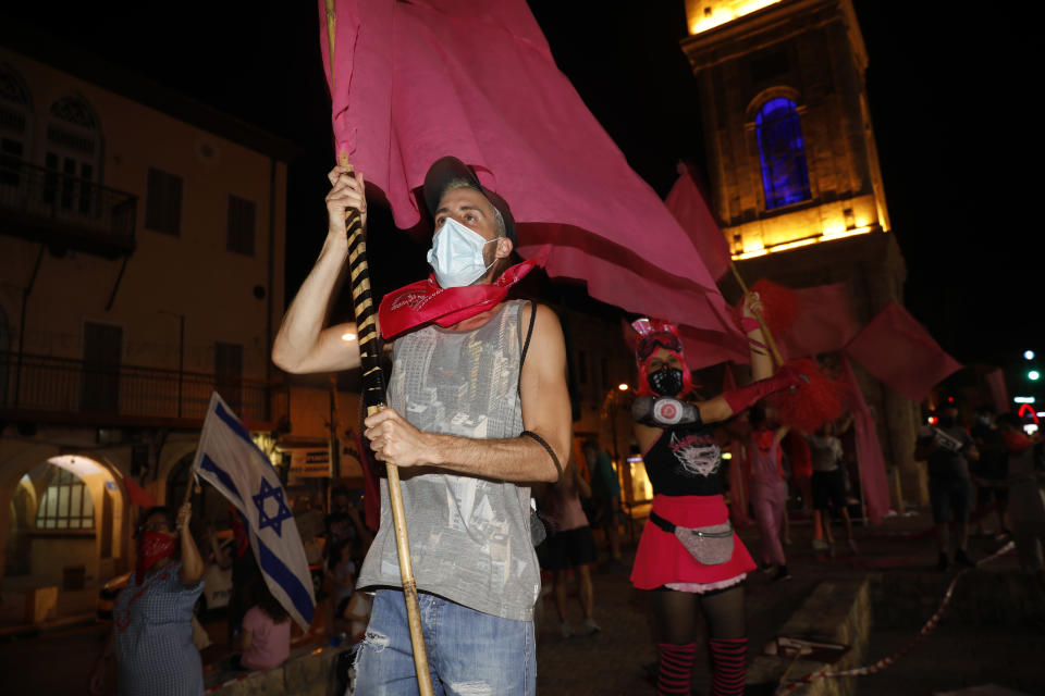 People chant slogans during a protest against Prime Minister Benjamin Netanyahu in Jaffa, Israel, Thursday, Oct. 8, 2020 during a nationwide lockdown to curb the spread of the coronavirus. The Israeli government has extended an emergency provision that bars public gatherings, including widespread protests against Netanyahu, for an additional week. (AP Photo/Ariel Schalit)