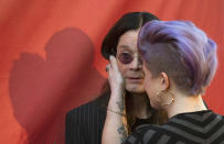 Kelly Osbourne wipes lipstick off the cheek of her father musician Ozzy Osbourne at the 10th Annual MusiCares MAP Fund Benefit concert at Club Nokia in Los Angeles, California May 12, 2014. REUTERS/Mario Anzuoni (UNITED STATES - Tags: ENTERTAINMENT)