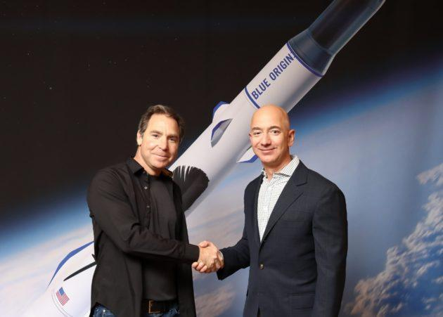 OneWeb executive chairman Greg Wyler and Blue Origin founder Jeff Bezos shake hands on a deal for satellite launches on Blue Origin's New Glenn rocket.
