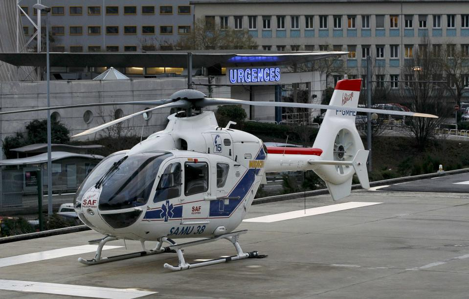 An helicopter stands outside the CHU Nord hospital in Grenoble, French Alps, where retired seven-times Formula One world champion Michael Schumacher is reported to be hospitalized after a ski accident, December 29, 2013. Schumacher suffered a head injury in a fall while skiing off-piste in the French Alps resort of Meribel on Sunday, an official said. The 44-year-old German was wearing a helmet and was conscious while being transported to a local hospital before later being transferred to to a better-equipped medical unit in Grenoble for further examinations. (REUTERS/Robert Pratta)