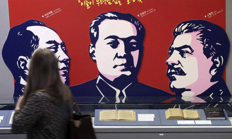 In this April 23, 2019 photo, a visitor looks at banner showing the late leaders, from left, of China's Mao Zedong, North Korea's Kim Il Song, Russia's Joseph Stalin as she tours the exhibition hall of the Korean War in Seoul, South Korea, Tuesday, April 23, 2019. North Korean leader Kim Jong Un's meeting with Russian President Vladimir Putin gives an intriguing twist to the global diplomatic push to resolve the nuclear standoff with North Korea, which appeared to hit a wall after a summit between Kim and President Donald Trump collapsed in February. (AP Photo/Lee Jin-man)