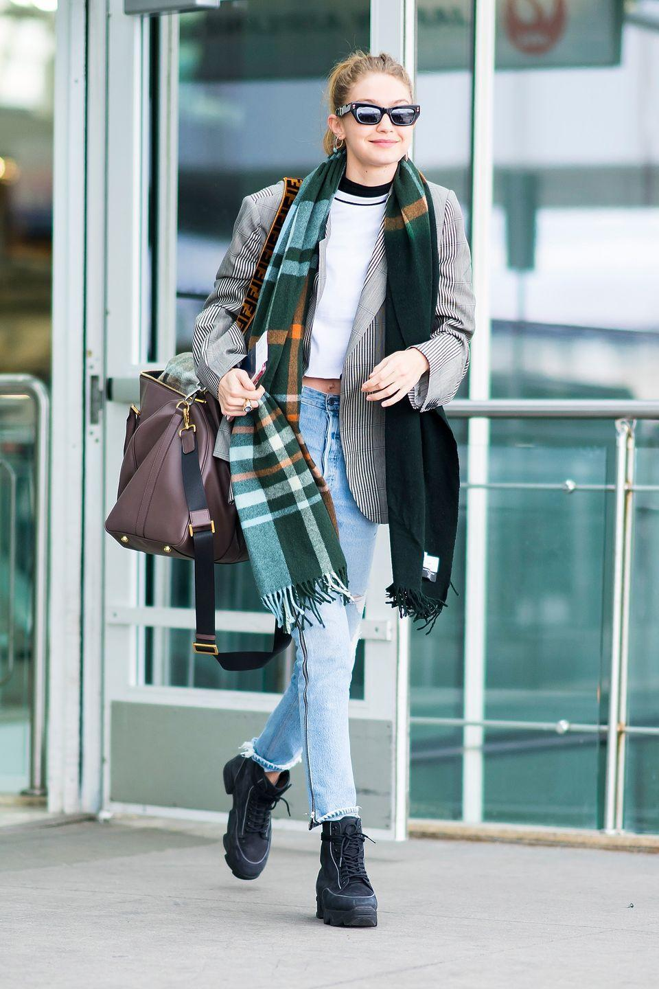 <p>wearing light-wash high waisted jeans, a white t-shirt, a striped blazer, a green plaid scarf, black lace-up boots, and a oversized leather shoulder bag.</p>