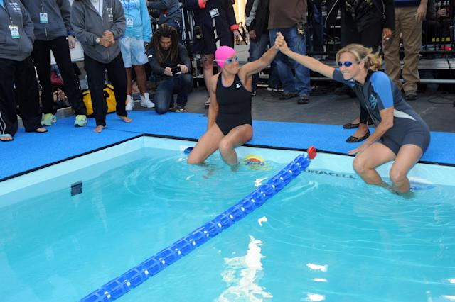 "IMAGE DISTRIBUTED FOR P&G - Long-distance swim legend Diana Nyad, left, high fives GMA anchor Lara Spencer before Nyad starts her 48-hour continuous ""Swim for Relief"" to support Hurricane Sandy recovery efforts, Tuesday, Oct. 8, 2013, in New York's Herald Square. The swim is raising funds for AmeriCares, a non-profit relief organization, with P&G brands such as Duracell, Tide and Secret underwriting the production costs to maximize the funds donated. (Photo by Diane Bondareff/Invision for P&G/AP Images)"