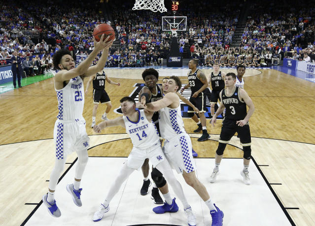 Kentucky's EJ Montgomery, left, grabs a Wofford rebound as Tyler Herro (14) holds back Wofford players during the first half of a second-round game in the NCAA mens college basketball tournament in Jacksonville, Fla., Saturday, March 23, 2019. (AP Photo/Stephen B. Morton)