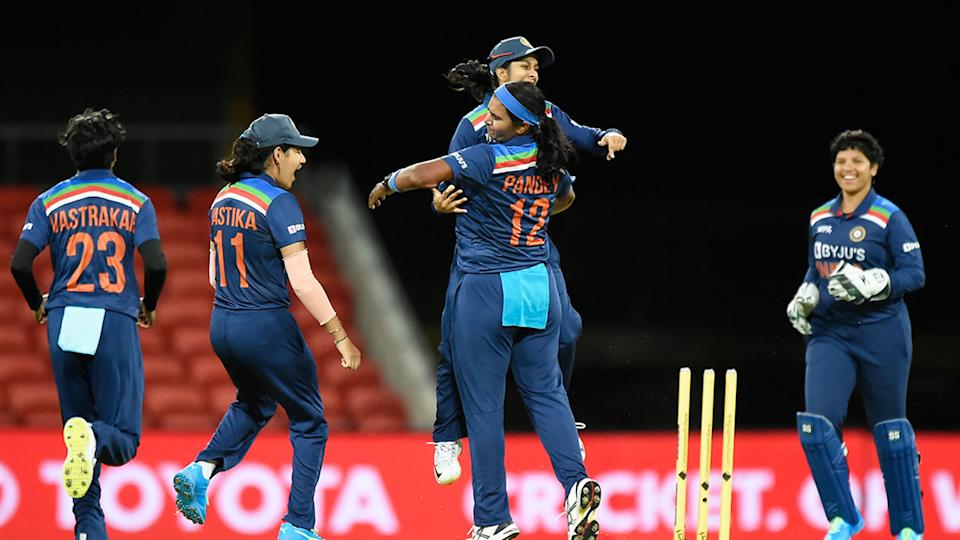 Seen here, Shikha Pandey celebrates with Indian teammates after taking the wicket of Alyssa Healy.