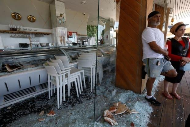Israelis stand outside a restaurant that was attacked the previous night in rioting in the Mediterranean city of Bat Yam last Thursday.