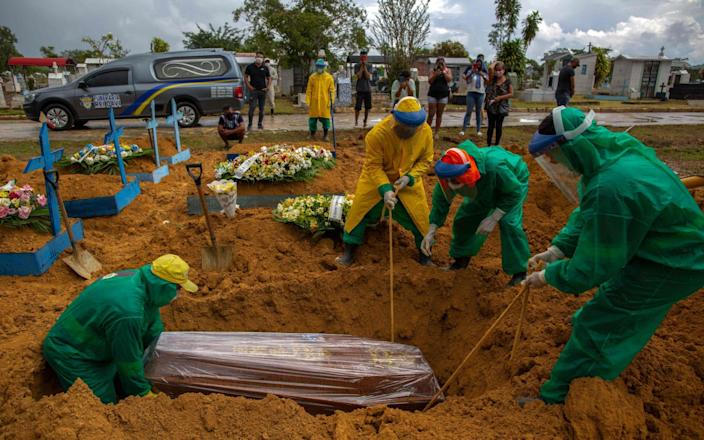 Gravediggers bury a Covid-19 victim while surrounded by relatives at the Nossa Senhora Aparecida cemetery in Manaus - Michael Dantas/AFP