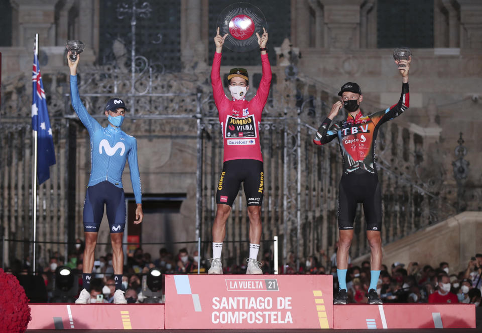 Vuelta race winner Primoz Roglic of Slovenia, centre celebrates on the podium alongside 2nd placed Magnus Cort Nielsen of Denmark, left and 3rd placed Thymen Arensman of the Netherlands at the end of the Vuelta Cycling race in Santiago, Spain, Sunday, Sept. 5, 2021. (AP Photo/Luis Vieira)