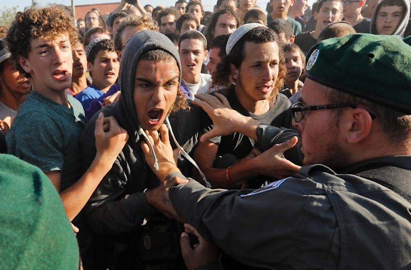 An Israeli police officer scuffles with activists as colleagues begin evicting 15 families from the Netiv Haavot settlement outpost in the occupied West Bank on June 12, 2018 in accordance with a Supreme Court order (AFP Photo/Menahem KAHANA)