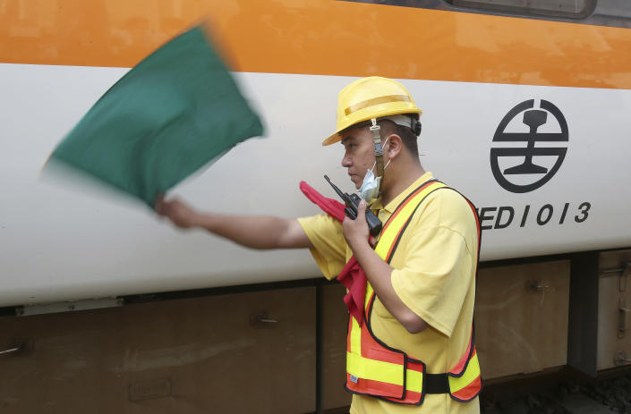 A worker guides to remove a part of the derailed train near Taroko Gorge in Hualien, Taiwan on Saturday, April 3, 2021. The train partially derailed in eastern Taiwan on Friday after colliding with an unmanned vehicle that had rolled down a hill, killing and injuring dozens. (AP Photo/Chiang Ying-ying)