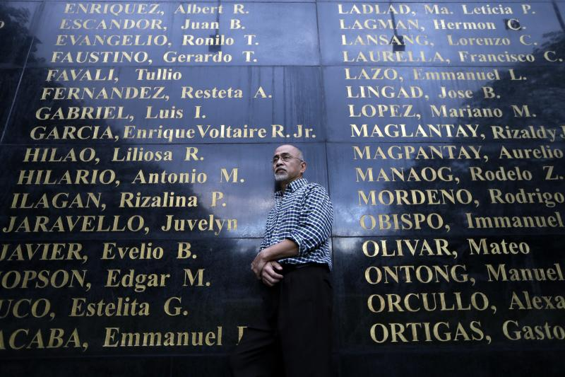 Fiipino poet Bonifacio Ilagan, one of hundreds of activists imprisoned during Martial Law period imposed by the late strongman Ferdinand Marcos, poses by the granite wall which is engraved with the names of Martial Law victims, including his sister Rizalina Ilagan, at the Heroes Shrine at suburban Quezon city, northeast of Manila, Philippines Monday Jan. 28, 2013. More than 9,000 victims will be awarded compensation using $246 million that the Philippine government recovered from Marcos' ill-gotten wealth. But all claims will still have to evaluated by an independent commission and the amount each will receive will depend of the abuse suffered. (AP Photo/Bullit Marquez)
