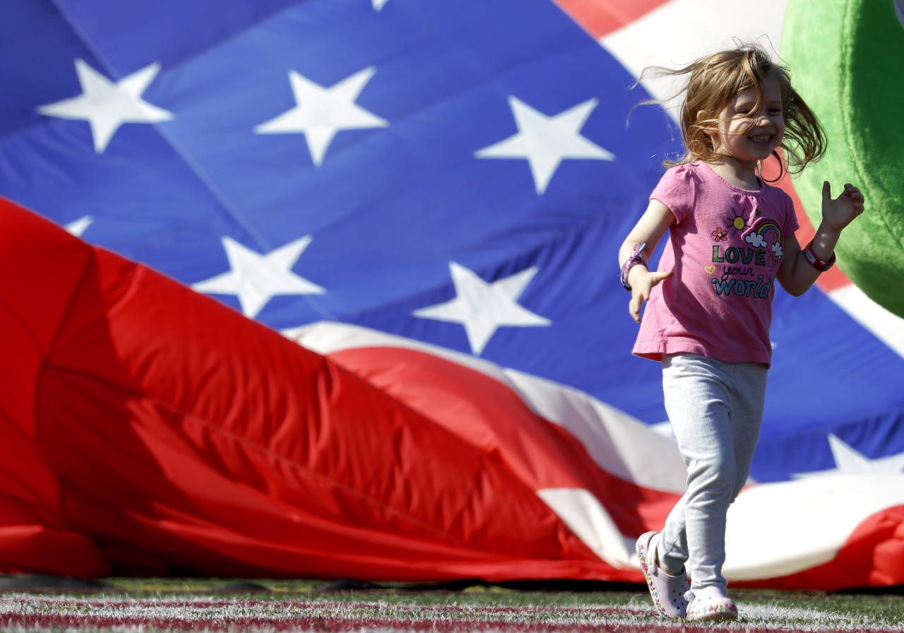 Sophie Katz, 4, of Hoboken, runs on the athletic field at Stevens Institute of Technology, where a large hot air balloon draped with the colors of the U.S. flag was being deflated, Tuesday, July 3, 2012, in Hoboken, N.J. The balloon, which is part of the Quick Chek New Jersey Festival of Ballooning held at the end of of July at Solberg Airport in Readington, N.J., flew over the athletic field in honor of the Fourth of July holiday. (AP Photo/Julio Cortez)